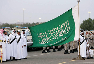 Members of Saudi al-Mujahdeen forces hold up the Saudi Arabia flag in Arafat